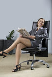 Portrait of businesswoman holding newspaper in office, smiling Stock Images