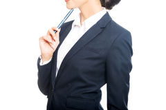 Portrait of businesswoman holding pen under chin Stock Photos