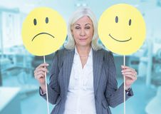 Portrait of a businesswoman holding smiley and sad faces Stock Photo