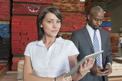 Portrait of businesswoman holding tablet PC while colleague using cell phone Royalty Free Stock Images