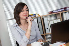 Portrait of businesswoman with laptop writes on a document Royalty Free Stock Photo