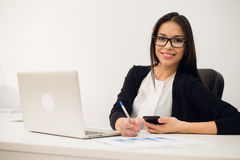 Portrait of businesswoman with laptop writes on a document at her office Stock Images
