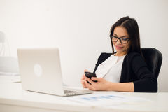 Portrait of businesswoman with laptop writes on a document at her office Royalty Free Stock Image