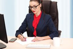 Portrait of businesswoman with laptop writes on a document at he Royalty Free Stock Image