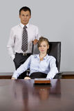 Portrait of businesswoman looking at businessman, sitting in office Royalty Free Stock Photo