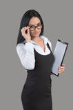 Portrait of businesswoman looking over glasses. Young woman with papers in her hand looking over glasses, indoors portrait on gray background Royalty Free Stock Images