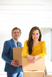Portrait of businesswoman and male colleague with cardboard boxes in new office Royalty Free Stock Photo