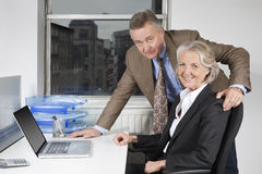 Portrait of businesswoman and man with laptop at desk in office Royalty Free Stock Photography