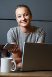 Portrait Of Businesswoman With Mobile Phone Working On Laptop In Royalty Free Stock Photography