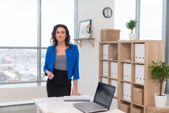 Portrait of businesswoman in office looking confident and smiling. royalty free stock photography