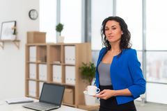 Portrait of businesswoman in office looking confident and smiling. stock photo