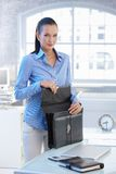 Portrait of businesswoman opening briefcase Stock Image