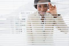 Portrait of a businesswoman peeking through blinds Royalty Free Stock Photos