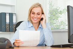 Portrait of a businesswoman phoning and reading Stock Image