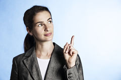 Portrait of businesswoman pointing upwards. Stock Photo