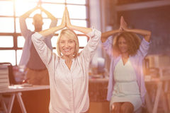 Portrait of businesswoman practicing yoga with coworkers Stock Photo
