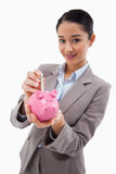 Portrait of a businesswoman putting a bank note in a piggy bank Royalty Free Stock Image