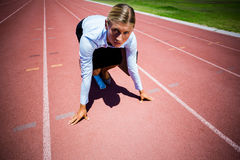 Portrait of businesswoman ready to run on running track Royalty Free Stock Photos