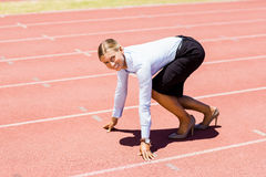 Portrait of businesswoman ready to run on running track Stock Image