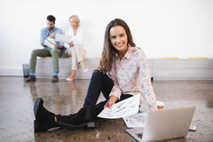 Portrait of businesswoman sitting by laptop on floor at creative office Stock Image