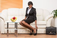 Portrait of businesswoman sitting on sofa at home. Businesswoman sitting in office putting shoes on Stock Images