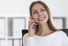 Portrait of businesswoman with a smartphone. Portrait of a smiling blond businesswoman in white in her office. She is on her phone and looking upwards. Concept Royalty Free Stock Image
