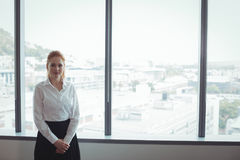 Portrait of businesswoman standing against window at office Stock Images
