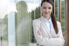 Portrait of businesswoman standing arms crossed by glass door Stock Photography