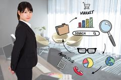 Portrait of businesswoman standing by various icons in office Royalty Free Stock Photos
