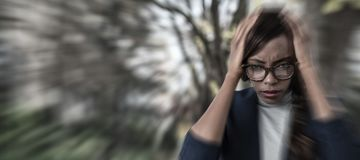 Composite image of portrait of businesswoman suffering from headache royalty free stock image