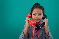 Portrait of businesswoman talking land line phones. Against blue background Royalty Free Stock Photography