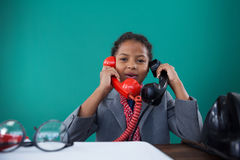 Portrait of businesswoman talking land line phones at desk. Portrait of businesswoman talking land line phones sitting at desk against blue background Royalty Free Stock Image