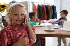 Portrait of businesswoman talking on mobile phone while colleagues working in background Stock Photos