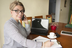 A portrait of a businesswoman talking on the phone looking into the camera and smiling. Stock Image