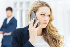 Portrait of businesswoman talking on phone in office Stock Photos