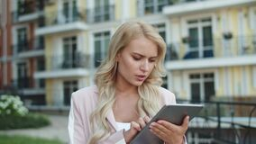 Portrait businesswoman walking in suit. Woman using tablet for work outside stock video footage