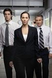 Portrait of a businesswoman walking with two businessmen Stock Photo