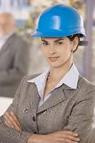 Portrait of businesswoman wearing hardhat. Standing with arms crossed, smiling confidently at camera Royalty Free Stock Image