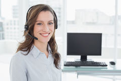 Portrait of businesswoman wearing headset in office Stock Photos