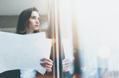 Portrait businesswoman wearing suit and holding papers in hands. Open space loft office. Panoramic windows background. Horizontal. Portrait businesswoman wearing royalty free stock images