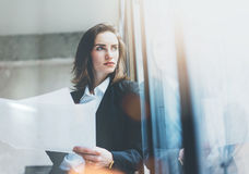 Portrait businesswoman wearing suit, talking smartphone and holding papers in hands. Open space loft office. Panoramic windows bac Royalty Free Stock Photos