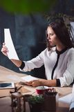 Portrait of a businesswoman who is working at office. And checking details of her upcoming meeting in her notebook and working at loft studio royalty free stock images