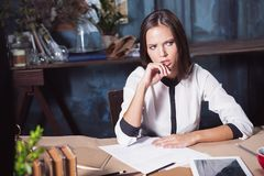 Portrait of a businesswoman who is working at office. And checking details of her upcoming meeting in her notebook and working at loft studio Stock Photo