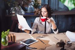 Portrait of a businesswoman who is working at office. And checking details of her upcoming meeting in her notebook and working at loft studio Stock Images