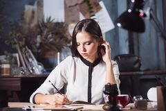 Portrait of a businesswoman who is working at office. And checking details of her upcoming meeting in her notebook and working at loft studio royalty free stock photography