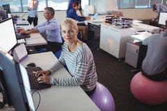Portrait of businesswoman working at desk while sitting on exercise ball. In office Royalty Free Stock Photography