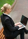 Portrait of a businesswoman working on laptop outdoors Stock Photo
