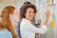 Portrait businesswoman writing on glass as colleagues looking at it Royalty Free Stock Images