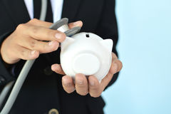 Portrait of Businesswomen with stethoscope and white piggy bank Stock Photo