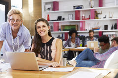 Portrait Of Businesswomen Working On Laptop In Busy Office Stock Photo